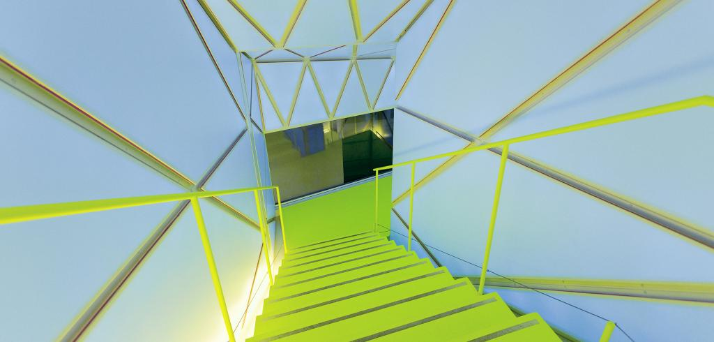 A stairwell with brightly colored metal stairs and struts at various angles