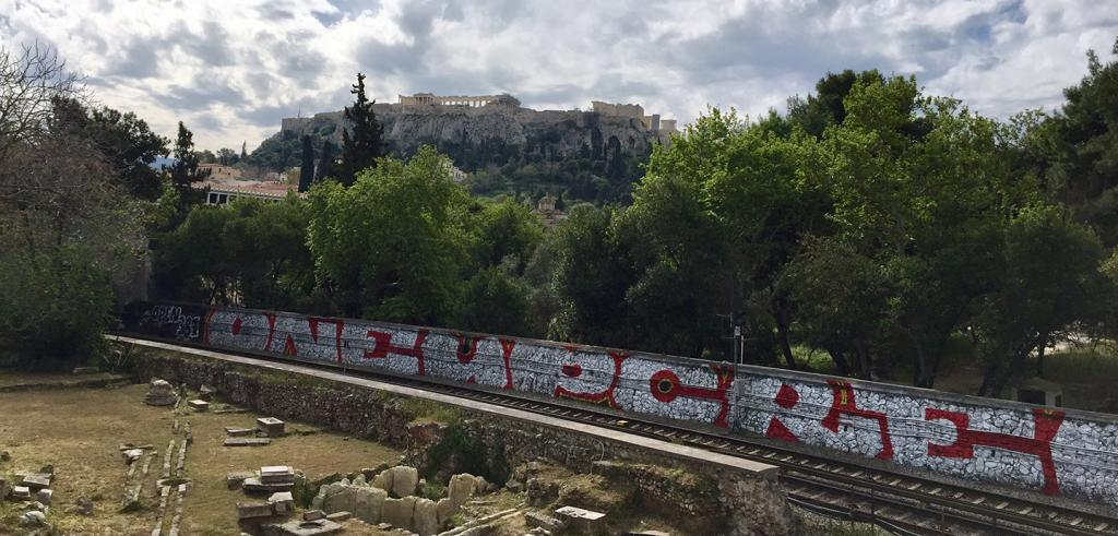 A distant view of the Parthenon in Athens, Greece with a graffitied wall and ruins in the foreground