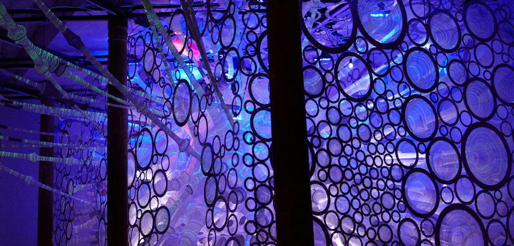 backlit installation of circular fabric items