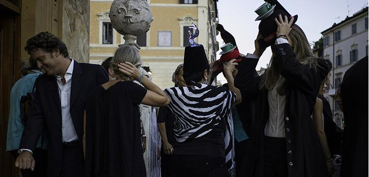 Photograph of people putting on unusual hats