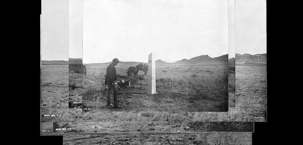 Man and animals next to a monument in the desert