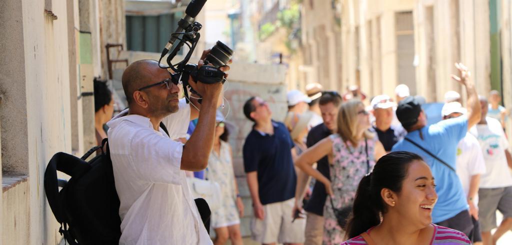 Filmmaker Kannan Arunasalam filming on the streets of Havana.