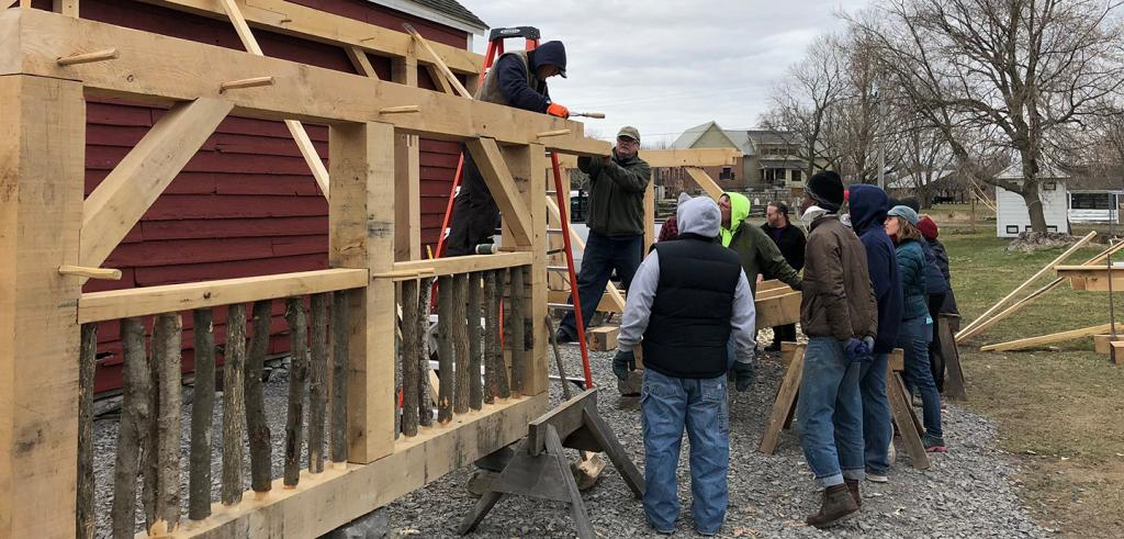 a group of people helping to build an outdoor structure