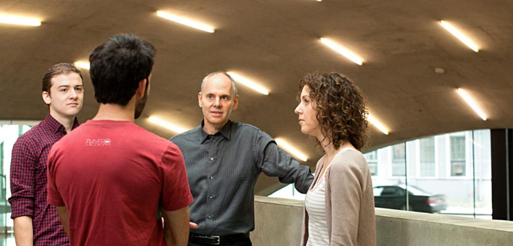 A college dean talking with students in Milstein Hall