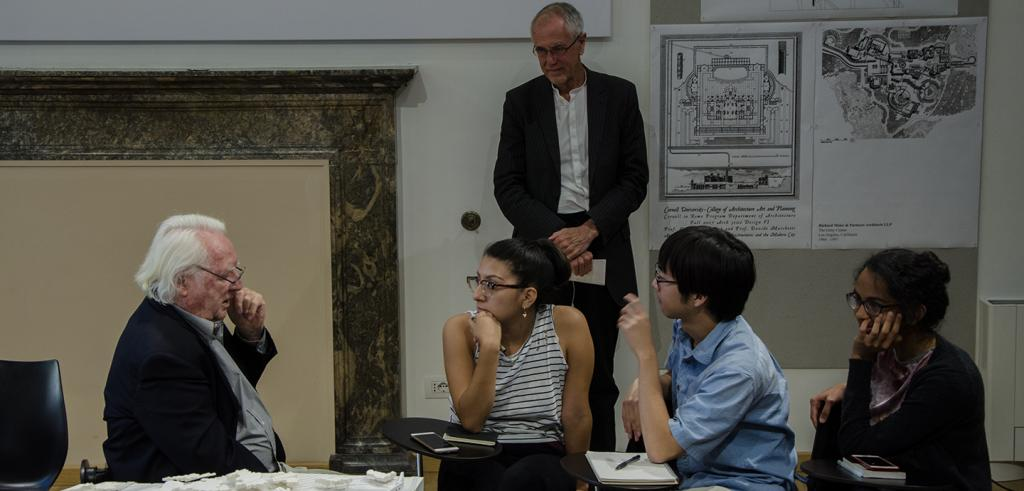 Image of three students at a table with two instructors and an architecture model
