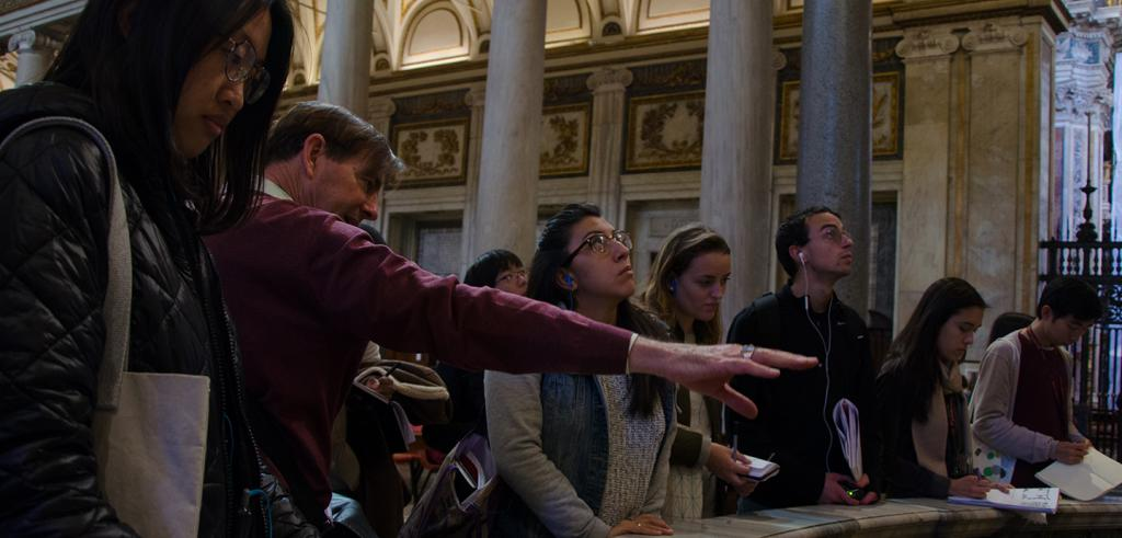 Several students inside a roman church with columns and chapels in the background, man at center with hand outstretched while speaking