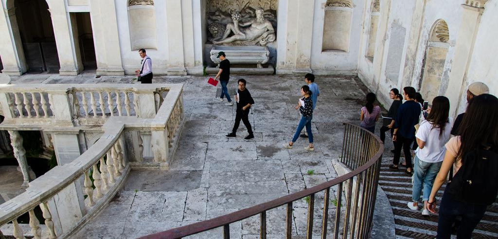 a group of people descending a spiral stair to a roman courtyard