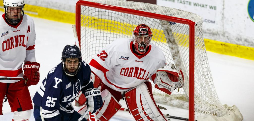 action shot of Cornell men's hockey game vs. Yale, Mitch Gillam in goal near two other players