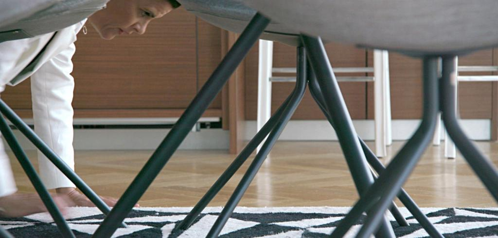 A woman crawling on the floor to straighten a rug