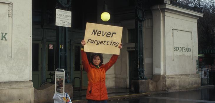 Woman in red coat holding up a sign that reads Never Forgetting