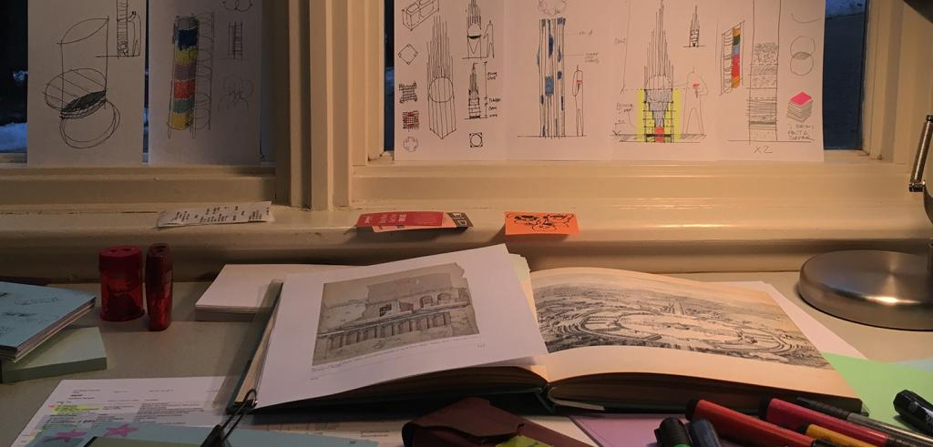 Open book and markers on a desk with architectural sketches on a windowsill
