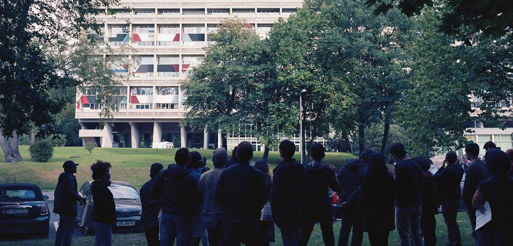 group of people standing and viewing a modernist apartment building from a distance