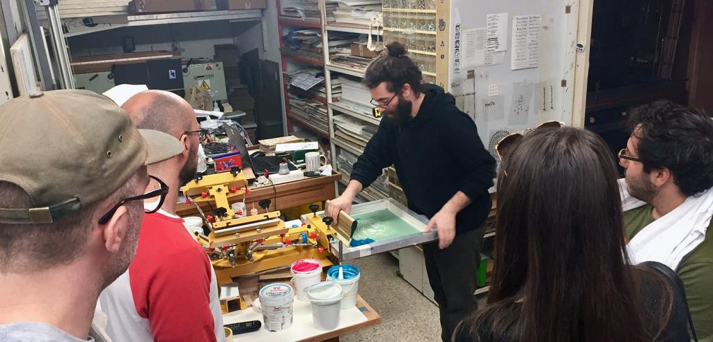 A group stands around a person demonstrating the screen printing process in an art studio