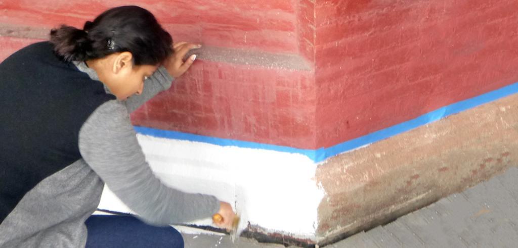volunteer working on the exterior finish of Auburn Castle