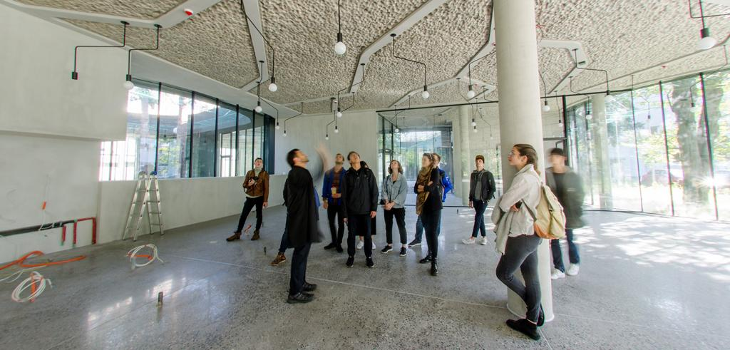 A group of people looking at the white ceiling inside of a building