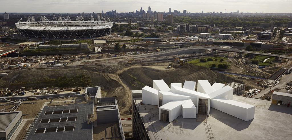 stadium and modern white building in a city scape