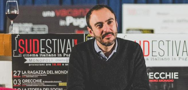 Man seated in front of posters for Italian film series
