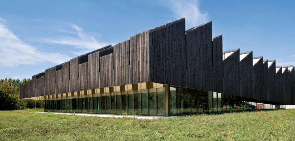 Two-story building, lower level of glass windows, upper level a series of tall, angled, dark wood clad shapes in a rows.