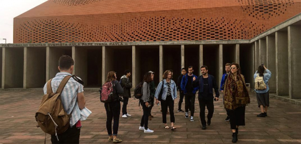 A group of people in the courtyard of a building with a geometric brick roof