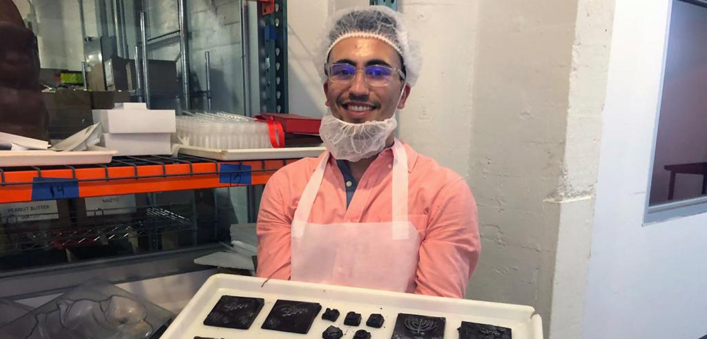 a man wearing hair and face nets holds a tray of chocolate