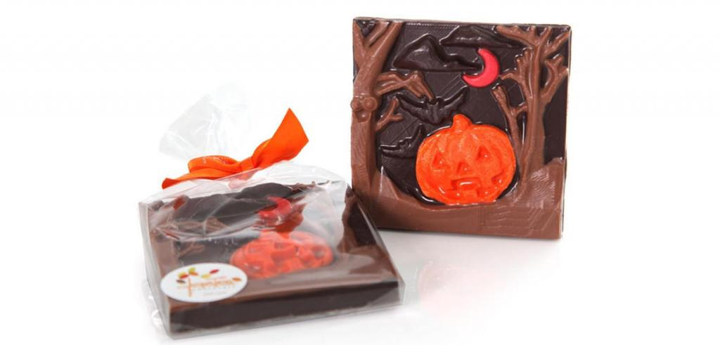 Two squares of chocolate candy decorated with Halloween shapes.