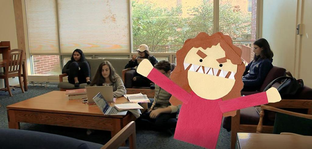 students seated in a lounge with a construction paper cut-out of a student in front.