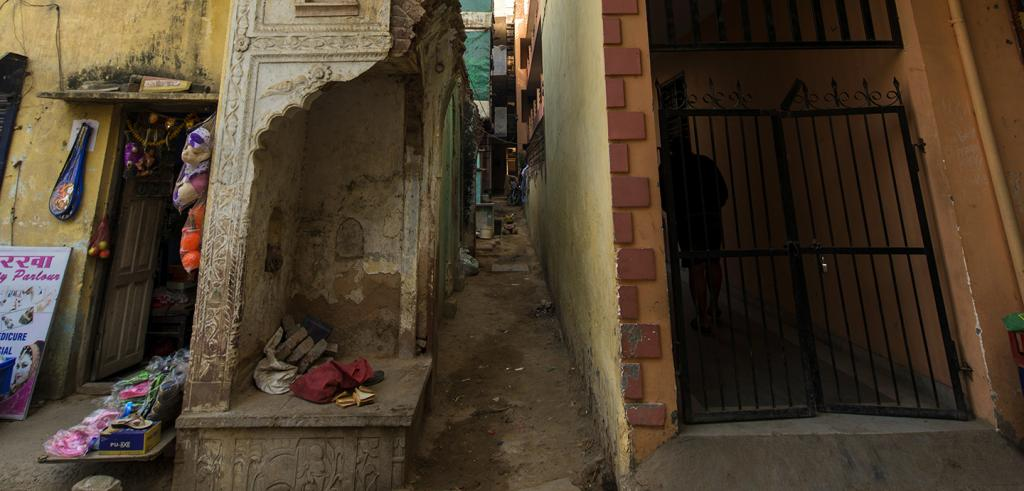 narrow alley and a gated doorway near crumbling walls in an Indian city