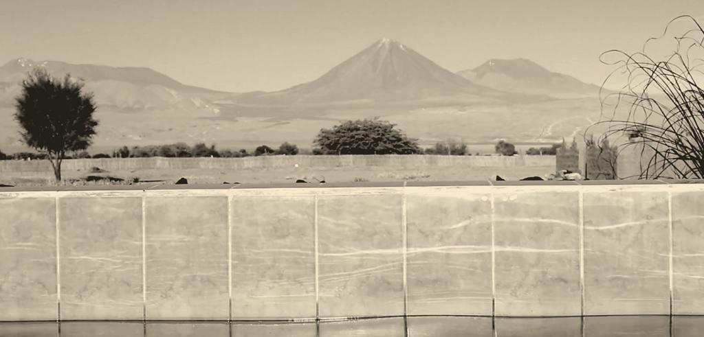 Landscape featuring mountains and a desert with a concrete fence against a river set in a sepia tone.