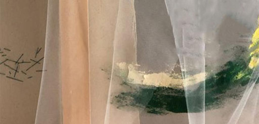 Cream colored sheer fabric against a grayish colored background with green, cream and yellow paint smeared across the right side.