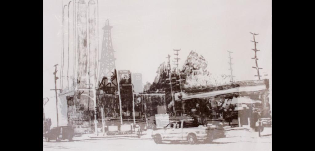 Faded sepia image of an oil field with large metal structures and several card by a street.