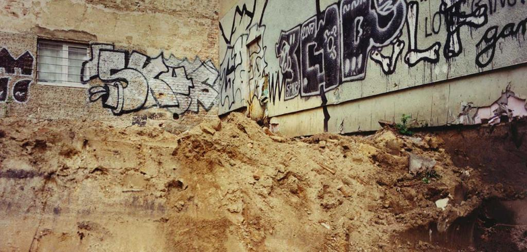 A concrete wall with crumbling pieces, black and white graffiti, and a large dirt pile in front of it.
