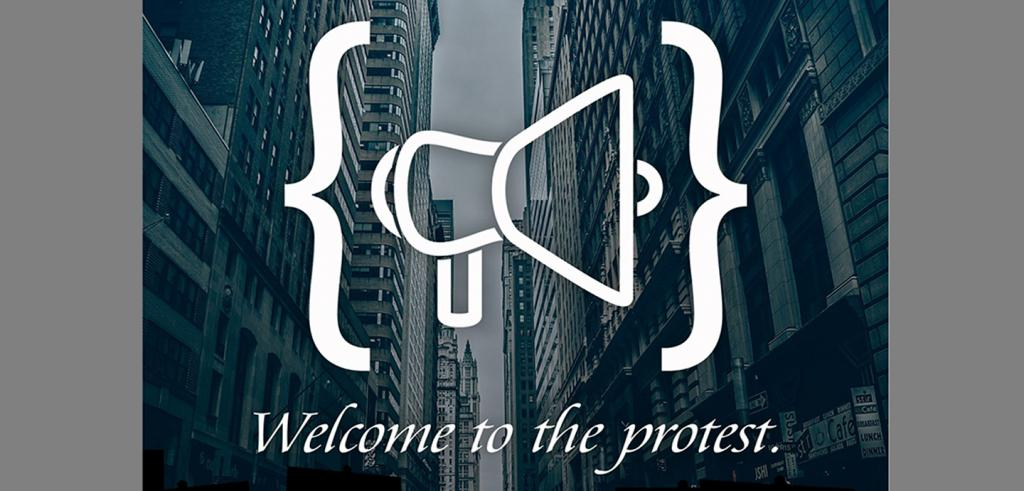 View down a city street with buildings on both sides with a white printed image of two brackets and a megaphone with white text welcome to the protest.