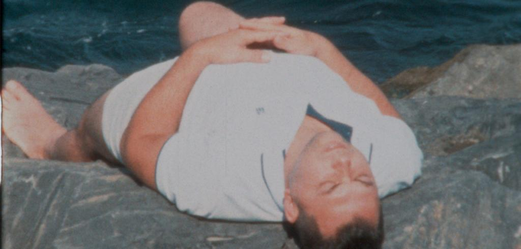 Man in a white collared shirt laying down on grey rocks by water.