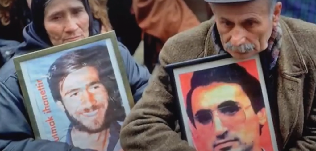 An older man and an older woman in a crowd holding framed photos of young men.