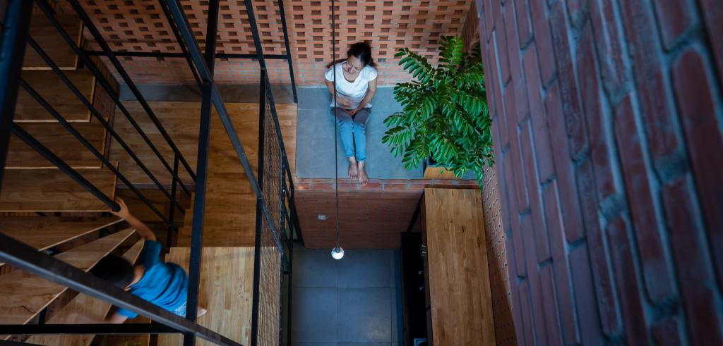 Brick wall on right and spiral staircase on left with woman sitting on landing next to green plant