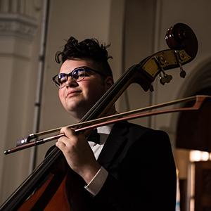 man with dark hair and glasses holding a cello and bow