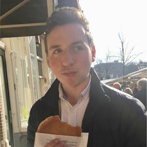 student with short hair, white shirt, jacket, holding a waffle