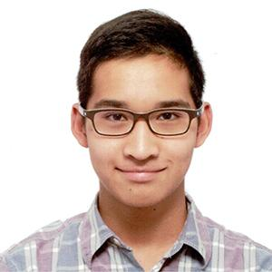 headshot of a young man with glasses wearing a checked shirt