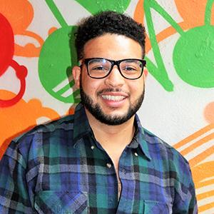 headshot of a man in glasses with a beard wearing a plaid shirt standing in front of a multicolor painting
