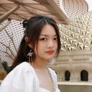 student with long dark hair white outfit outside among architecture