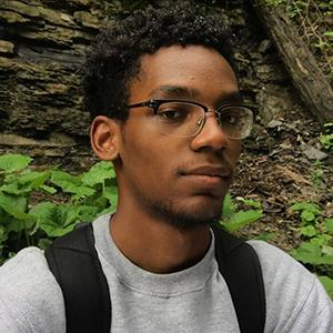 headshot of a young man wearing a backpack
