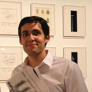 man with dark hair and glasses standing in front of a wall of framed pictures