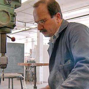 portrait of a man wearing a blue jacket using a drill press