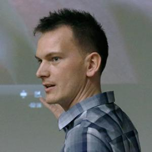 side view of a man with short dark hair wearing a plain shirt pointing to the side