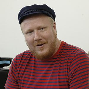 man with reddish beard wearing a black cap and striped shirt
