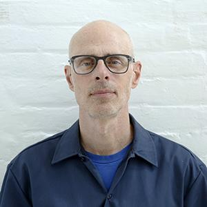 headshot of bald man with glasses standing in front of a white brick wall