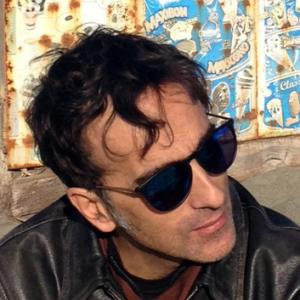man wearing sunglasses looking off to the left in front of a colorful background