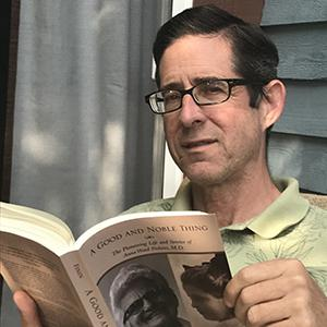 A man with dark hair and black-framed glasses, wearing a green collared shirt and reading a book.