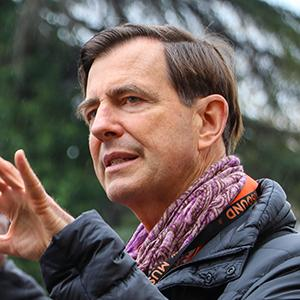 headshot of a man with brown hair wearing a multicolor scarf and gesturing with his hand