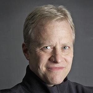 A man's face with short, blonde hair.